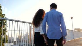 走在桥梁的男人和妇女年轻夫妇夏令时 日落光 在企业衣裳的时髦的愉快的对 股票录像
