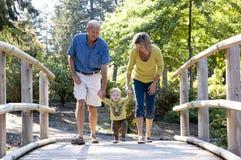 走在桥梁的祖父母和孙子 库存照片