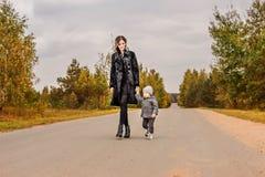 走在森林公路的家庭母亲和她的小儿子搭车在风雨如磐的天空下 库存图片