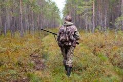 走在森林公路的猎人 免版税库存照片