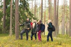 走在森林里和享受一好秋天天的年轻愉快的朋友 免版税库存照片