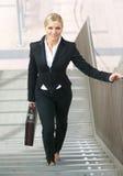 走在楼上与袋子的确信的女商人 免版税库存图片