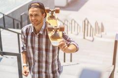 走在楼梯的快乐的男性溜冰者 免版税库存照片