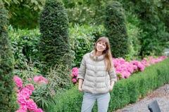 走在欧洲庭院里的愉快的美丽的年轻studient女孩 她查看照相机 库存照片