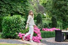 走在欧洲庭院里的愉快的美丽的年轻studient女孩 她查看照相机 库存图片