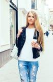 走在欧洲街道上的一个年轻美丽的白肤金发的女孩的画象用咖啡 室外 温暖的颜色 图库摄影