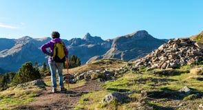 走在比利牛斯山的妇女远足者在Pic Ossau附近 免版税库存照片