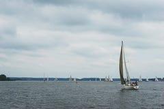 走在池塘,湖的一条航行游艇,在一个多云夏日 免版税图库摄影