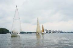 走在池塘,湖的一条航行游艇,在一个多云夏日 库存图片