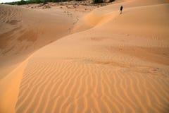 走在沙丘,蓝天的一个人 库存照片