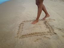 走在沙子海滩的妇女把脚印留在沙子 女性脚特写镜头细节在巴西的 免版税库存照片