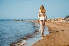 走在沙子海滩的妇女把脚印留在沙子 免版税图库摄影
