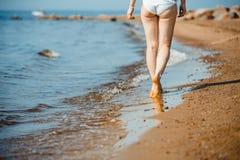 走在沙子海滩的妇女把脚印留在沙子 库存照片