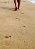走在沙子海滩的妇女离开脚印 免版税库存图片