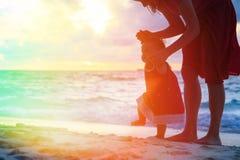 走在沙子的母亲和小女儿靠岸 库存图片