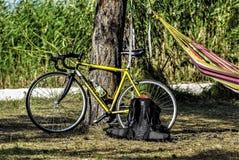 走在沙子的男性自行车车手、日出和湖或者河背景 库存图片