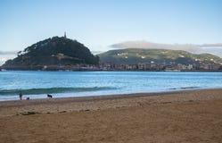 走在沙滩的人们有在山urgull的看法在大西洋外耳咆哮,圣・萨巴斯蒂安,巴斯克国家,西班牙 免版税库存照片