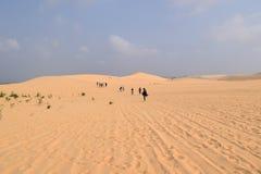 走在沙漠的人们 库存图片