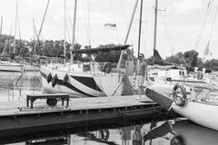 走在河小游艇船坞的旅客近有被折叠的风帆的小船 年轻时兴的人起动河旅途乘游艇 人和 免版税库存照片