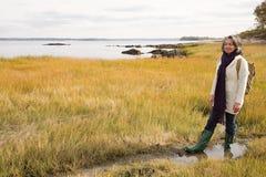 走在沼泽地的成熟妇女 图库摄影