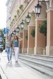 走在沿大厦的边路的旅游夫妇 免版税库存照片