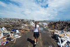 走在泥泞的路的女孩在垃圾堆 库存图片