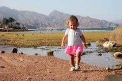 走在海岸的孩子反对backgroun山 免版税库存图片