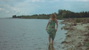 走在海岸的赤足微笑的妇女 股票视频