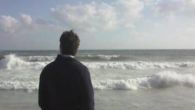 走在海洋海滩的一个被设想的人 股票录像