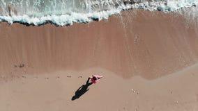 走在海滨的女孩 走在海滩的女孩空中顶视图的关闭 红色成套装备的妇女在海岸线 在沙子的脚印 影视素材