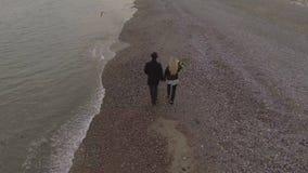 走在海滨的约会夫妇握手,女孩运载的花,日期 股票录像