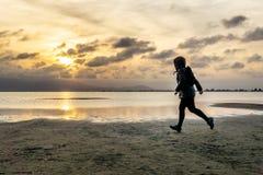 走在海滩的一名无法认出的妇女的剪影在日落 免版税库存图片