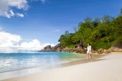 走在海滩的一名美丽的妇女 免版税图库摄影