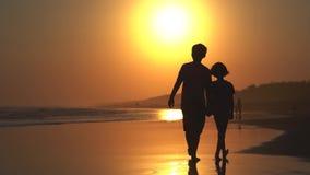 走在海滩的两个孩子剪影  股票录像