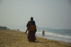 走在海滩的印度妇女摊贩 库存照片