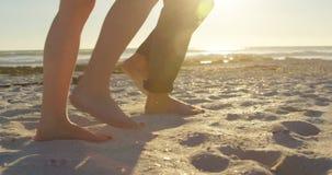 走在海滩的夫妇的低部分在一好日子4k 股票录像
