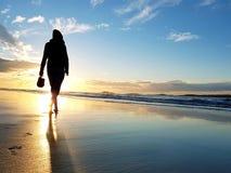 走在海滩的妇女剪影 免版税库存照片