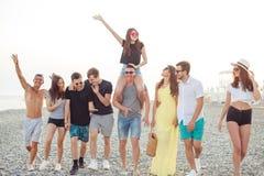 走在海滩的小组朋友,获得乐趣,妇女扛在肩上供以人员,滑稽的假期 免版税库存图片