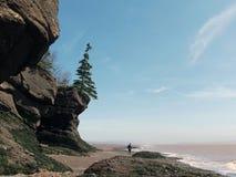 走在海滩的峭壁下的人 免版税库存照片