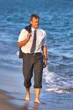 走在海滩的年轻商人在水中在西班牙布拉瓦海岸 图库摄影