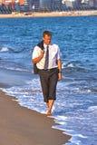 走在海滩的年轻商人在水中在西班牙布拉瓦海岸 免版税库存照片