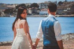 走在海滩的年轻婚姻的夫妇 免版税库存图片