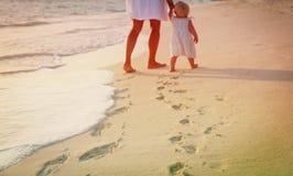 走在海滩的母亲和女儿把脚印留在沙子 库存照片