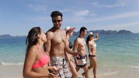 走在海滩谈话,年轻游人小组通信美好的晴朗的风景的人们 股票录像