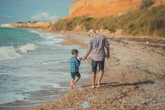 走在海边与穿时髦的衣裳的逗人喜爱的儿子的石头海滩的英俊的父亲梦想接触场面享受夏时toget 库存照片