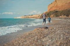 走在海边与穿时髦的衣裳的逗人喜爱的儿子的石头海滩的英俊的父亲梦想接触场面享受夏时toget 免版税库存照片