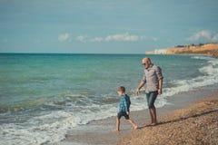 走在海边与穿时髦的衣裳的逗人喜爱的儿子的石头海滩的英俊的父亲梦想接触场面享受夏时toget 图库摄影