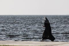 走在海边的年轻回教女孩 免版税库存图片