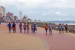 走在海滩前的被铺的散步的人们 免版税库存图片