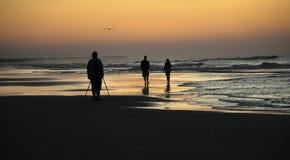 走在海滩剪影的人们 库存照片